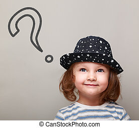 Thinking cute kid with big question sign above looking up on...