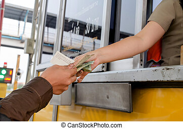 Man paying money at toll booth in thailand