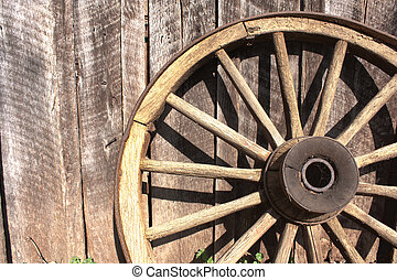 Wooden wagon wheel leaning against a weathered barn