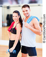 two smiling people in the gym - fitness, sport, training,...