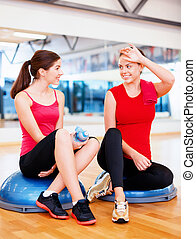 two smiling women sitting on the half balls - fitness,...