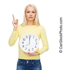 student with wall clock and finger up - time, education and...