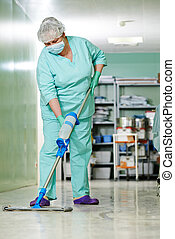 Woman cleaning hospital hall - Adult cleaner maid woman with...