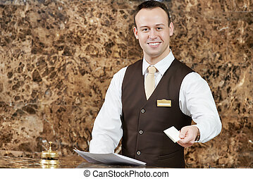 hotel worker with key card - smiling male receptionist...