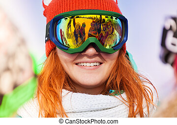 Happy young woman in ski mask with reflection of her friends...