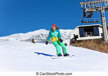 Girl in ski mask sliding on the snowboard down the mountain...