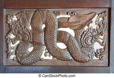 Wood carving of nagas