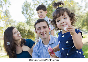 Cute Young Baby Girl Blowing Bubbles with Family in Park -...