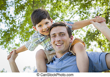 Father and Son Playing Piggyback in the Park - Mixed Race...