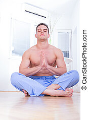 Handsome bare chested man doing yoga - good looking young...
