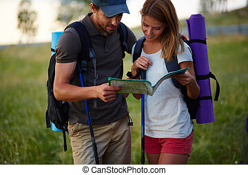 Looking at map - Portrait of couple of hikers looking at map...