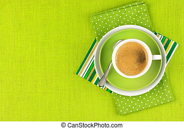 Cup of coffee - White cup of coffee on green linen Top view...