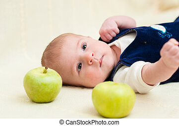 baby lying on the bed with appl