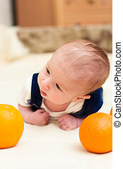 baby lying on the bed with oranges