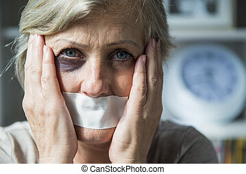 Domestic violence - Senior woman with black eye and tape on...