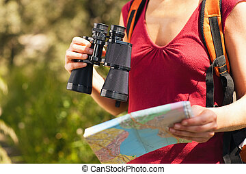 woman hiking - cropped view of female bird watcher holding...