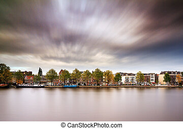 Amstel cloudscape - Long exposure image of the houses at the...