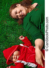 Young mother and her child lie on the green grass