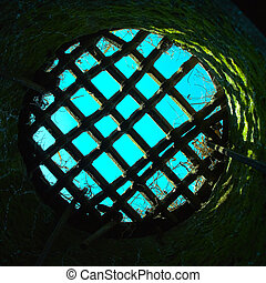 Blue sky through the round prison window
