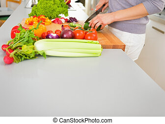 Closeup on young housewife cutting vegetables