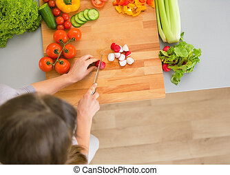 Young housewife cutting vegetables