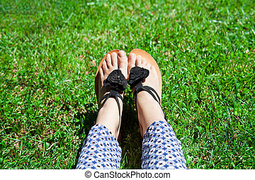 feet in green grass - feet in sandals in green grass