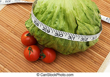 Weight Loss - A head of lettuce and tomatoes with measuring...