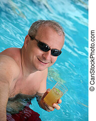 Mature man in the pool - A happy mature man in the pool with...