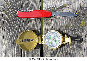Compass and pocket knife on the wooden background
