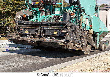 Asphalt paving machine - A working blue and black asphalt...