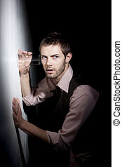 Handsome young man using glass to eavesdrop - Handsome young...