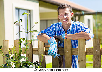 young man leaning on fence relaxing - young man leaning...
