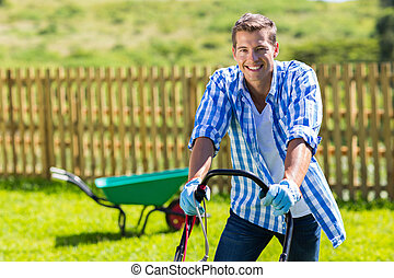 happy man mowing lawn at home garden
