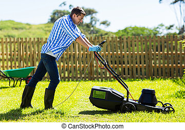 man mowing lawn in the backyard - cute man mowing lawn in...