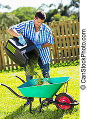 young man emptying lawnmower grass into a wheelbarrow after...