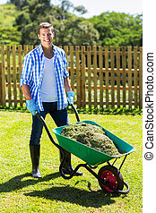 young man pushing wheelbarrow full of grass after cleaning...