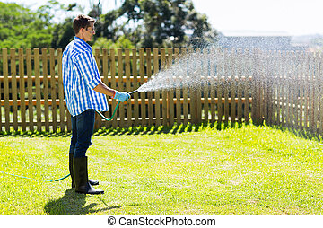 young man watering backyard lawn using hosepipe