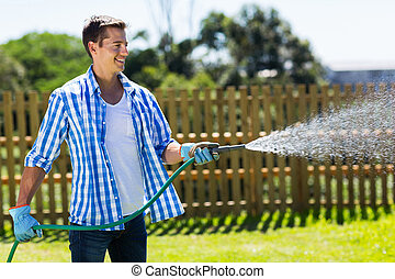 man watering garden - cheerful man watering home garden