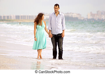young couple walking beach discussing problems - young...