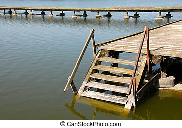 Downstairs into water - old wooden stairs on yellowish lake...
