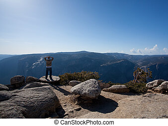 Male hiker looking at view from Yosemite Peak - View from...