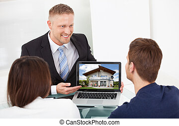 Advisor Showing House Picture To Couple On Laptop - Smiling...