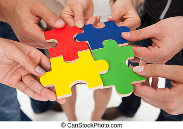 Businesspeople Joining Puzzle Pieces - Cropped image of...