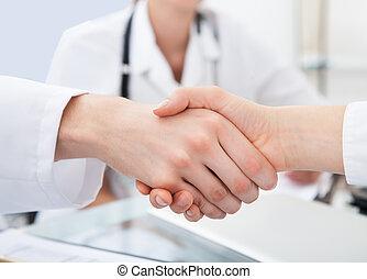 Doctors Shaking Hands At Desk - Cropped image of doctors...
