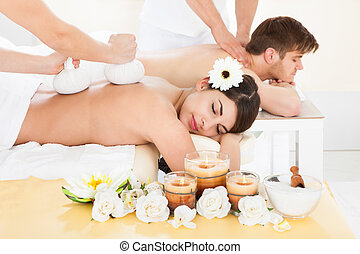 Couple Receiving Back Massage In Spa - Cropped image of...