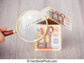 Fingers Holding Magnifying Glass To Analyze Euro House -...