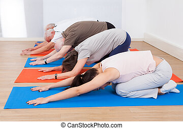People Performing Yoga At Gym - Row of people performing...