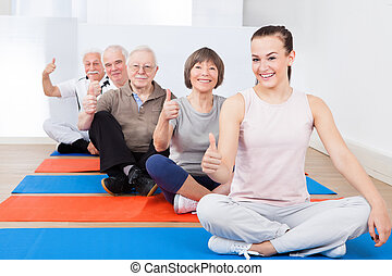 Confident Trainer With Senior Customers At Gym - Portrait of...