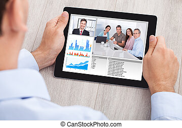 Businessman Video Conferencing With Team On Digital Tablet -...