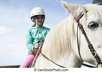 Horse riding - Child on white horse. Horse trekking,...